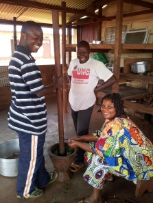 Pounding cassava leaves for pondu; Jeanne adds the garlic
