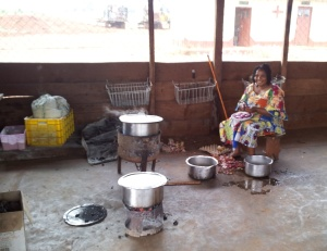 Jeanne preparing the goat stew; the rice is already cooking on the second brazier